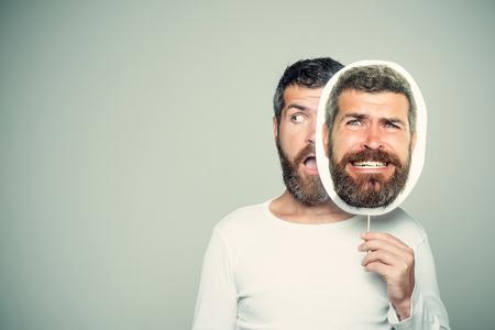 床屋のファッションと美しさ。灰色の背景に男やあごひげの男。長いあごひげと口ひげを持つ男。怖くて驚いた顔のヒップスターは、肖像画のネー 写真素材