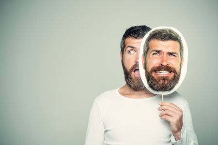 Barber fashion and beauty. Guy or bearded man on grey background. Man with long beard and mustache. Hipster with scary and surprised face hold portrait nameplate. Feeling and emotions., copy space