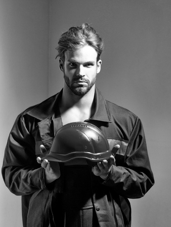 ハンサムな男ビルダー建設石工職人修理工職人の職人はボイラースーツでブロンドのひげを生やした男性は、灰色の背景に手にオレンジ色のハード