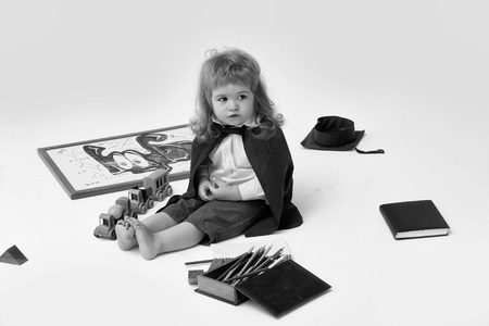 Little boy child in black academic gown playing with drawing school board holding marker near box with colored pencils isolated on white background Archivio Fotografico
