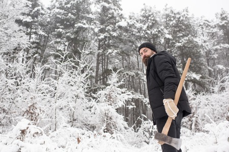 Man lumberjack with ax. skincare and beard care in winter, beard warm in winter. Camping, traveling and winter rest. Temperature, freezing, cold snap, snowfall. Bearded man with axe in snowy forest.