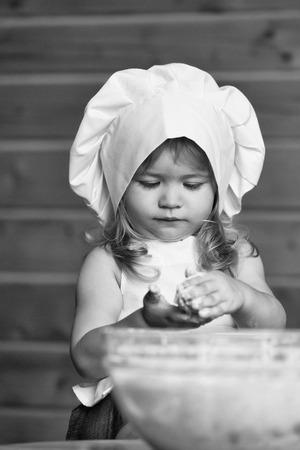 Kleines nettes Baby oder Kind mit glücklichem Gesicht in der weißen Kochuniform mit Chefhut und -schürze, die Teig mit Mehl in der Glasschüssel in der Küche auf hölzernem oder Holzhintergrund knetet Standard-Bild - 93010787
