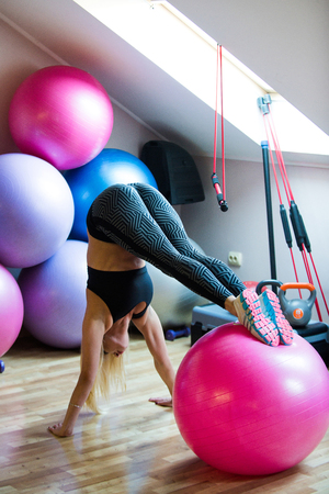 Sport, fitness, yoga. Woman athlete do handstand with legs on fit ball. Girl in sportswear training on fitball in gym. Balance, endurance, strength concept. Workout, training, activity. Stock Photo