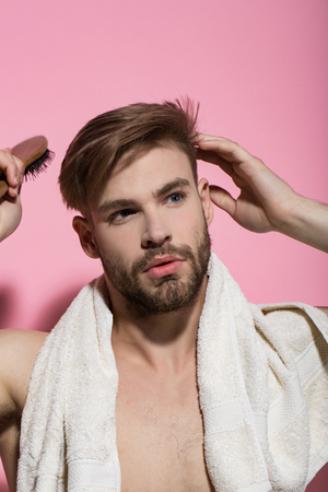 Haircare, wellness, health. Man brush hair with hairbrush on pink background. Beauty, grooming, hygiene. Macho with bath towel on neck. Morning routine concept.