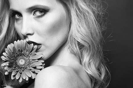 Closeup portrait of one beautiful sexy passionate blonde woman with long curly hair in studio with bare shoulder and brigt makeup holding gerbera flower near face on pink backdrop, horizontal picture