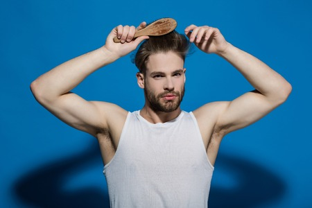 Fashion, underwear, style. Man brush hair with hairbrush on blue background. Haircare, hairstyle concept. Beauty, grooming, hygiene. Macho with bearded face and haircut in white singlet. Stock Photo