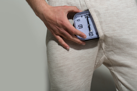 Alarm clock show six oclock in male underwear on grey background. Potency, desire concept. Health, strength, power. Stock Photo