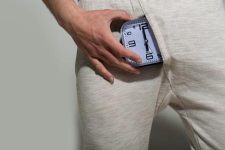 De wekker toont zes uur in mannelijk ondergoed op grijze achtergrond. Potentie, verlangen concept. Gezondheid, kracht, kracht. Stockfoto