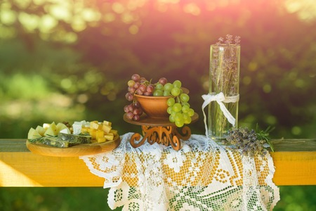 Grapes, cheese, lavender flowers, vase on white tablecloth on wooden board on natural background. Still life on summer day outdoor. Food, appetizer, cuisine concept.