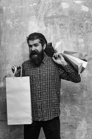 Happy bearded man, caucasian hipster, with long beard and moustache in red plaid shirt holding colorful paper shopping bags on beige wall background