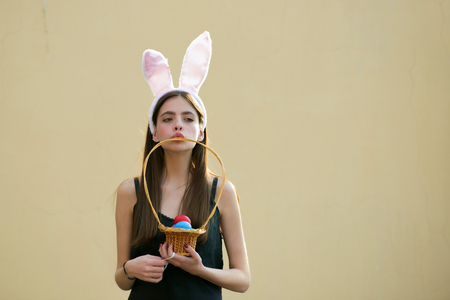 Easter girl with rosy bunny ears on beige background. Woman holding wicker basket with colored eggs. Fertility and rebirth concept. Easter tradition and symbol. Spring holiday celebration, copy space 版權商用圖片 - 93014193