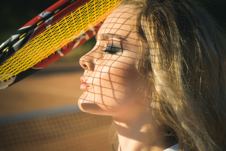 Girl athlete with net shadow on face on sunny day. Woman player with tennis racket on sunny day. Beauty, look, skincare. Sport, game concept. Activity, energy, health.