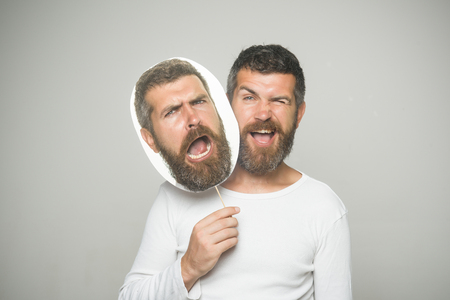 Feeling and emotions. Hipster with winking and sad face hold portrait nameplate. Barber fashion and beauty. Guy or bearded man on grey background. Man with long beard and mustache. Imagens
