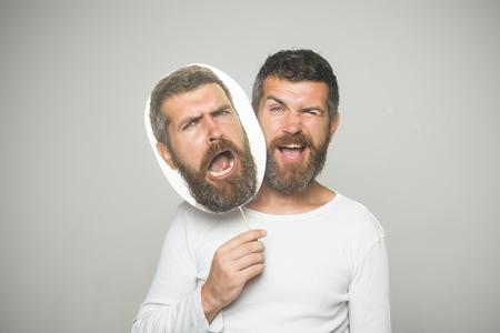 Gevoel en emoties. Hipster met knipogen en droevig gezicht houdt portret naamplaatje. Kapper mode en schoonheid. Man of bebaarde man op grijze achtergrond. Man met lange baard en snor.