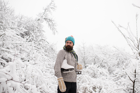 Winter sport and rest. Christmas. Temperature, freezing, cold snap, snowfall. skincare and beard care in winter. Man in thermal jacket, beard warm in winter. Bearded man with skates in snowy forest. Stock Photo