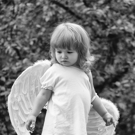 small cute baby boy with blonde long hair in white feathered angel wings and cloth outdoor on green natural background