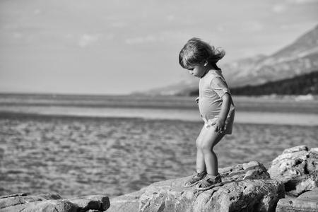 Mignon bébé enfant avec des cheveux blonds bouclés en chemise verte joue à la plage de la mer rocheuse sur la journée d & # 39 ; été Banque d'images - 93012987