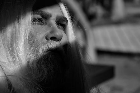 長い銀のひげと髪の長いドルイド老人は、ぼやけた背景にしわと顔に明るい光を持つ