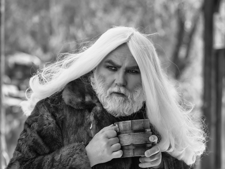 長い灰色の髪とひげを持つドルイド老人は、ぼやけた背景に手に木製のマグカップと毛皮のコートで