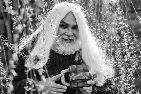 長い灰色の髪とあごひげを持つドルイド老人は、自然の背景に黄色の花の咲く晴れた日に手に木製のマグカップで笑顔に