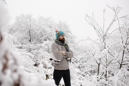 Bearded man with skates in snowy forest. skincare and beard care in winter. Man in thermal jacket, beard warm in winter. Temperature, freezing, cold snap, snowfall. Winter sport and rest, Christmas. Stock Photo