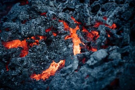 검은 화산재 배경에 용암 불꽃입니다. 마그마 질감 녹은 바위 표면. 화산, 불, 지각. 위험, 위험, 에너지 개념입니다. 형성, 지질학, 자연, 환경. 스톡 콘텐츠