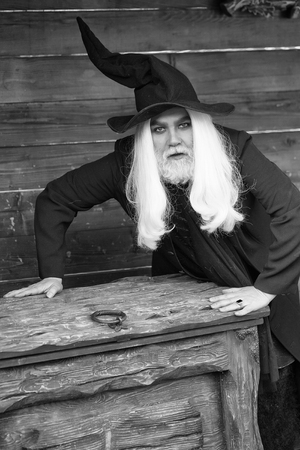 Old man wizard with long grey hair beard in black costume and hat for Halloween standing near wooden chest or trunk box on log house background Reklamní fotografie