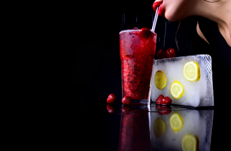 Cocktail with strawberry for young girl isolated on black. Bar and restaurant, lemonade. woman drink cocktail with ice cube. Party and summer vacation. Thirst and refresh, copy space