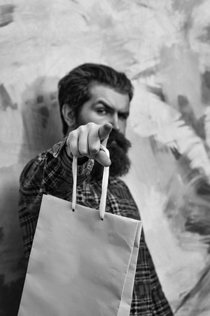 Serious bearded man, caucasian hipster, with long beard and moustache in red plaid shirt pointing finger with rosy paper shopping bag on abstract yellow and pink wall background