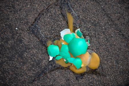 アスファルトの背景に壊れたイースターエッグ。黄色い黄身を持つ緑色の卵殻。不妊と再生の概念。春休みのお祝い。イースターの伝統とシンボル