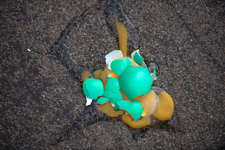 Easter egg broken on asphalt background. Green colored eggshell with yellow yolk. Fertility and rebirth concept. Spring holiday celebration. Easter tradition and symbol. Stok Fotoğraf