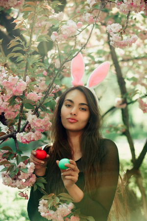 장미 빛 토끼 귀와 꽃가루에 화창한 날에 꽃이 만발한 사쿠라 꽃 나무에서 색 계란, 녹색 및 빨강을 들고하는 오래, 갈색 머리 소녀. 부활절. 봄