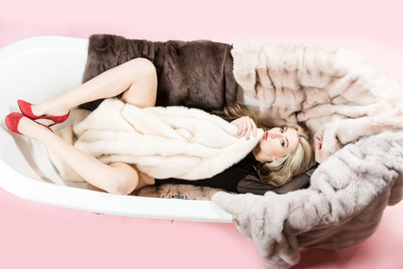 Skincare, spa, wellness. Woman in red stilettos on sexy legs on fur in bathtub. Winter fashion, beauty, look. Luxury, wealth, lifestyle concept. Girl relax on fur coats in bath on pink background.