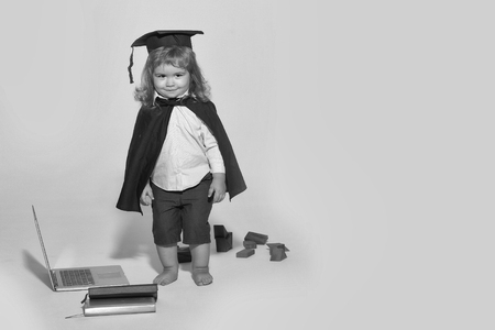 Small boy child with long blond hair in blue shirt black graduation gown and cap playing with wooden blocks near notebook and diaries isolated on white background Imagens - 93196040
