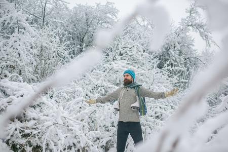 Winter sport and rest, Christmas. Bearded man with skates in snowy forest. Temperature, freezing, cold snap, snowfall. skincare and beard care in winter. Man in thermal jacket, beard warm in winter. Stock Photo