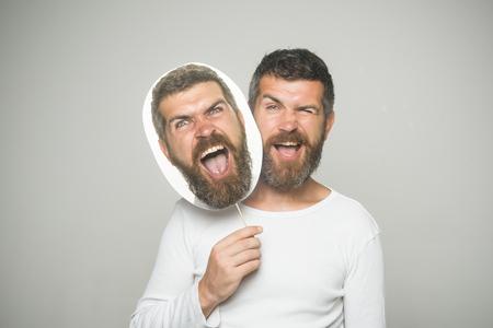Gevoel en emoties. Hipster met knipogen en boos gezicht houden portret naamplaatje.