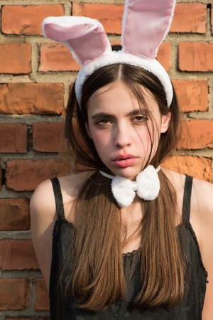 Easter girl posing on red brick wall. Woman with rosy bunny ears and bow. Fashion model with long brunette hair in black dress. Easter holiday celebration concept