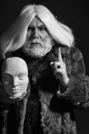 真面目な顔に長いあごひげを持つ古いドルイドひげの男と毛皮のコートで白い彫刻の頭を手に持ち、暗い背景にリングを持つ 写真素材