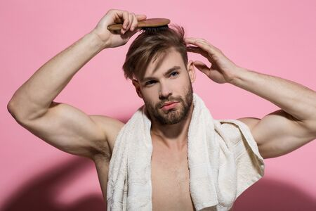 Morning routine concept. Macho with bath towel on sexy chest. Beauty, grooming, hygiene. Haircare, wellness, health. Man brush hair with hairbrush on pink background.