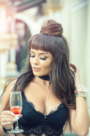 Woman holding glass of wine outdoors. Girl with long brunette hair in black lace bustier. Drinking alcohol concept. Cocktail party or holiday celebration. Bad habit and addiction.