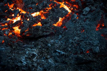 Magma textured molten rock surface. Lava flame on black ash background. Volcano, fire, crust. Formation, geology, nature, environment. Danger, hazard, energy concept. 写真素材