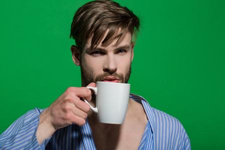 Mens met kop op groene achtergrond. Warme drank, dieet, gezondheid. Ochtend routine concept. Vrijgezel in blauwe peignoir met mok. Ontbijt, koffie of thee tijd. Stockfoto