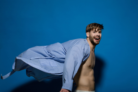 Happy bachelor with sexy torso in flying bathrobe. Man smile in dressing gown on blue background. Home clothes, leisure wear. Spa, wellness, grooming. Fashion, style concept. Stock Photo