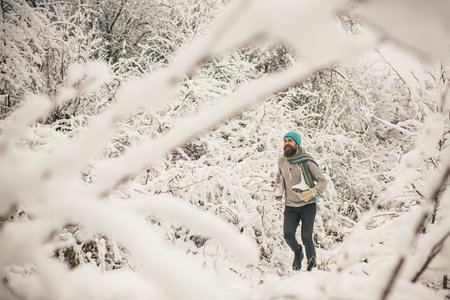 Man in thermal jacket, beard warm in winter. skincare and beard care in winter. Bearded man run with skates in snowy forest. Temperature, freezing, cold snap, snowfall. Winter sport, Christmas.