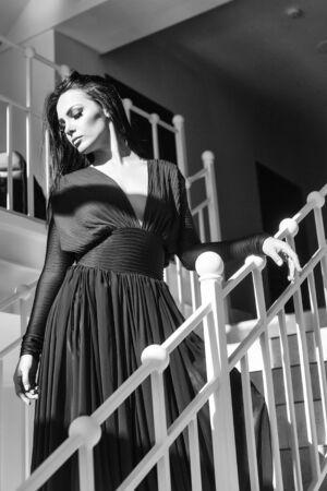 계단에 우아한 빨간 드레스에 갈색 머리 머리를 가진 젊은 아름다운 여자