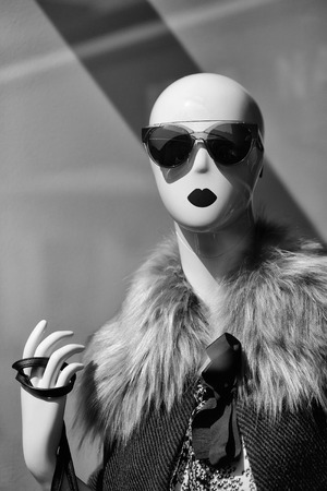 Fashion female mannequin bald in glamorous sunglasses and fur coat in shop on grey background Stock Photo