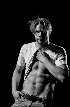 Handsome man or unshaven macho, bodybuilder, with stylish blond hair, haircut, in white tshirt showing sexy, muscular torso with six packs and abs, biceps, triceps, striptease on black background