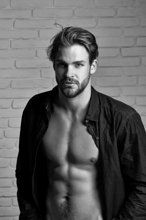 Sexy young handsome bearded man or guy with bare muscular chest and torso in black shirt on white brick wall background