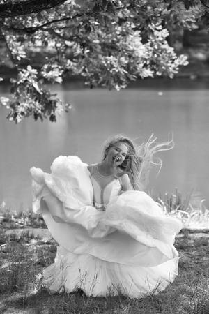 klein meisje jongen met lang blond haar en mooi lachend blij gezicht in prom prinses witte jurk staande zonnige dag buiten in de buurt van water