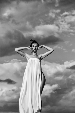 꽤 젊은 여자 또는 여자 섹시 한 흰 드레스에 슬림 시체 denuded 맑은 파란 하늘 배경 위에 자연에 포즈